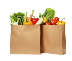 Paper bags with fresh vegetables on white background