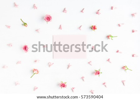Paper blank and pink flowers on white background. Mockup with flowers. Flat lay, top view.