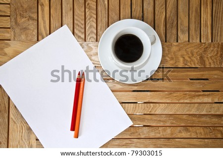 Paper blank Sheet, color pencil and a cup of coffee on a wooden table.