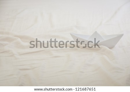 Paper Boat in a Calm White Bed sheet Sea.