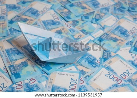 paper boat on  background of money-Russian rubles. The concept of savings for travel, vacations, dear vacation #1139531957