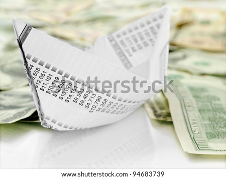 Paper Boat. Origami  paper boat made from financial  document on money background