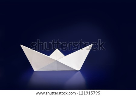 Paper boat . Origami paper boat on dark blue background