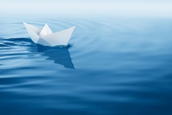 paper boat sailing on blue water surface