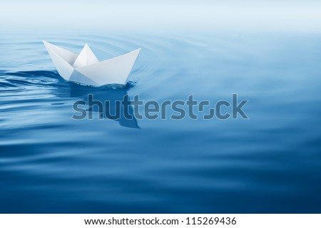 paper boat sailing on blue water surface - stock photo