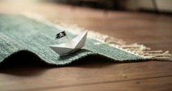 Paper Boat with Jolly Roger on Carpet Waves