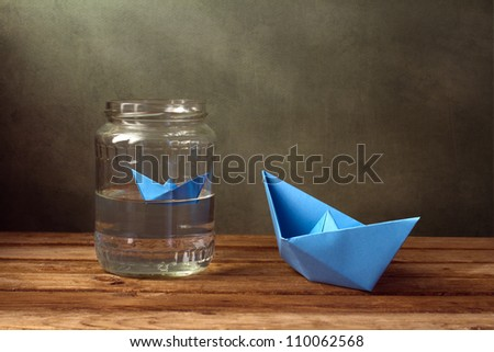 Paper boats and jar with water on wooden table - stock photo