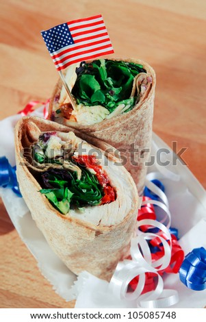 Paper bowl of chicken wrap sandwiches topped with a flag from the United States of America, and red, white and blue ribbons