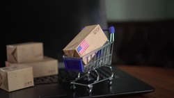 Paper box with a flag of United States of America in a shopping cart on a laptop. Online shopping. International E-commerce
