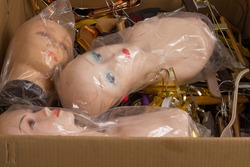 Paper box with female mannequin heads with makeup without hair in plastic bags and assorted hangers. Delivery of goods for purchases during the coronavirus. Shop of commercial equipment.