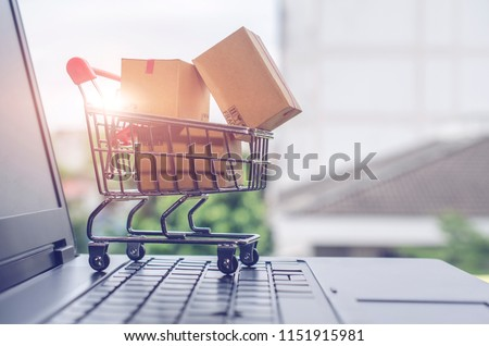 Paper boxes in a shopping cart on a laptop keyboard.Easy shopping with finger tips for consumers.Online shopping and delivery service concept.