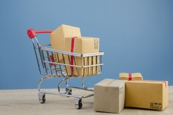 Paper boxes in a shopping cart on wood table.on blue wall background.concept online shopping.