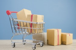 Paper boxes in a shopping cart on wood table,on blue wall background.concept online shopping.