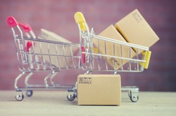 Paper boxes in a shopping cart on wood table,on brick wall background.concept online shopping.