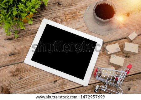 Paper boxes in shopping carts on desks and tablets, The concept of e-commerce, e-commerce or electronic commerce is a transaction of buying or selling products or services online via the internet.