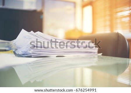 Paper business documents of unfinished stacked on office desk archive,in archive analyzing the market and considers on the size of future profits on table office. #676254991