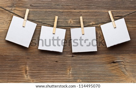 Paper card and clothes peg on a wooden background