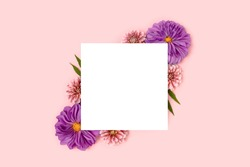 Paper card mockup with border frame made of dahlia flowers on a pink pastel background. Floral creative layout with copyspace.