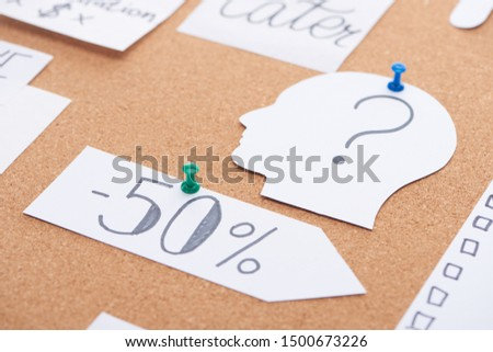 paper card with minus fifty percent discount text pinned on cork office board #1500673226