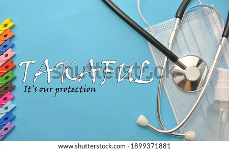 Paper clip, stethoscope , face mask hand sanitizer and handwriting ' TAKAFUL'  and word 'It's our protection' on isolated blue background.Takaful is insurance for muslim.Healtcare and medical concept. Stock fotó ©
