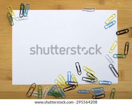 paper clips and blank paper on wooden background