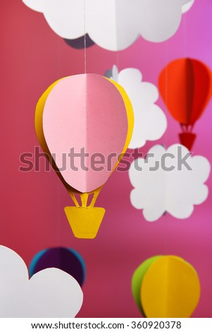 Paper clouds and airship on purple background