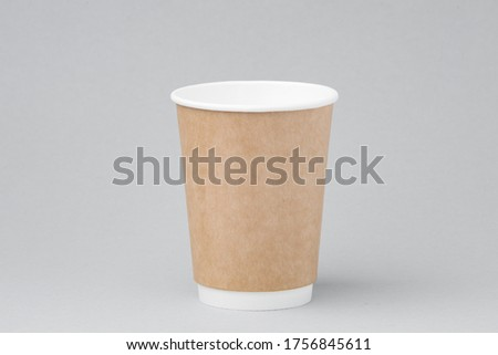 Photo of Paper coffee container on gray background. Takeaway drink cap container. Template of drink cup for your design. Free space for input text, image, and logo.