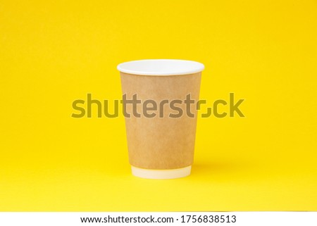 Photo of Paper coffee container on orange background. Takeaway drink cap container. Template of drink cup for your design. Free space for input text, image, and logo. Colored background.