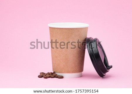 Photo of Paper coffee container with black lid and coffee beans on pink background. Takeaway drink cap container. Template of drink cup for your design. Free space for input text, image, and logo.