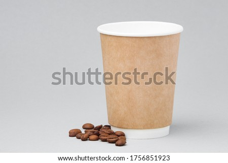 Photo of Paper coffee container with coffee bean on a gray background. Takeaway beverage container. Drink cup template for your design. Free space for entering text, image and logo.