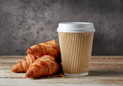 paper coffee cup and croissants on wooden table