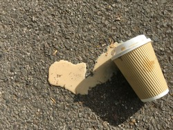 paper coffee cup with lid on lying on road  with white coffee with milk spilt out on ground on sunny afternoon with shadow