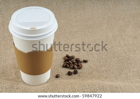 Paper coffee cup with safety cardboard collar on jute background with a big copy space