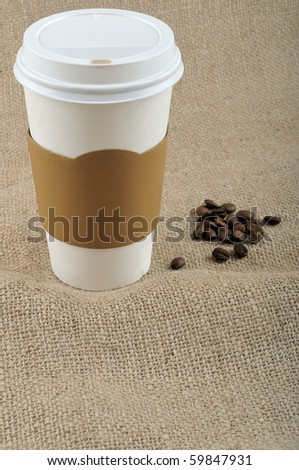 Paper coffee cup with safety cardboard collar on jute background with a big copy space in front