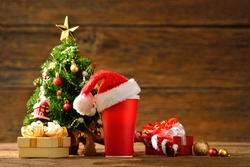 Paper coffee cup with Santa's hat on top surrounded by Christmas decorations on wooden background