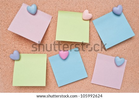 Paper color blank notes on cork board texture and  lovely Heart-shaped pins.