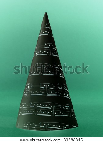 Paper cone with christmas carol notes over green background - stock photo
