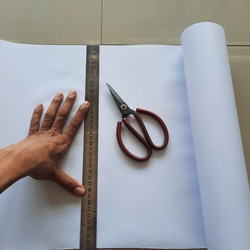 paper craft education,hand holding a ruler and measuring the paper to cut with scissors