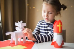 paper craft for kids. DIY toy Saint Nicholas and white horse for sinterklaas day. create art for children. girl glues horse.