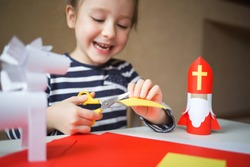 paper craft for kids. DIY toy Saint Nicholas and white horse for sinterklaas day. create art for children. happy girl cuts paper.