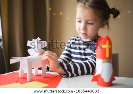 paper craft for kids. DIY toy Saint Nicholas and white horse for sinterklaas day. create art for children. girl glues horse. Stock photo ©