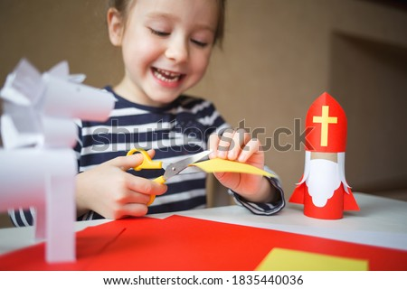 paper craft for kids. DIY toy Saint Nicholas and white horse for sinterklaas day. create art for children. happy girl cuts paper. Stock photo ©