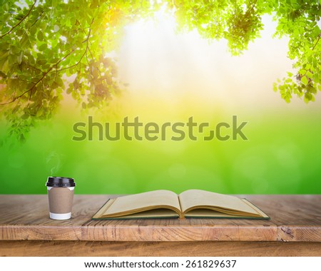 Paper cup of coffee and book on Wood table in nature