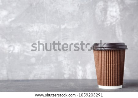 Paper cup with drink on grey wooden table #1059203291