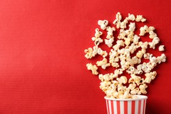 Paper cup with popcorn on color background
