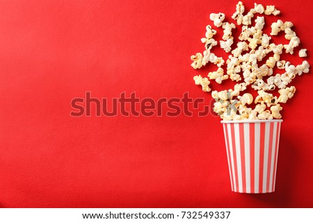 Paper cup with popcorn on color background #732549337
