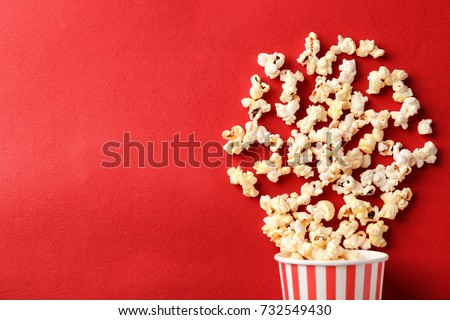 Paper cup with popcorn on color background - Shutterstock ID 732549430
