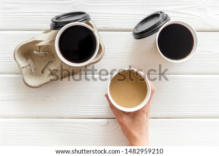 paper cups with black coffee and cappuccino in hand cappuccino to take away on white wooden background top view #1482959210