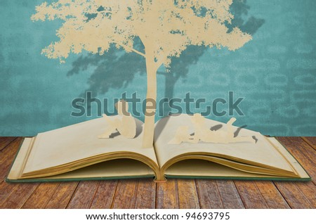 Paper cut of children read a book  on old book - stock photo