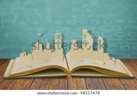 Paper cut of  cities with car and plane on old book